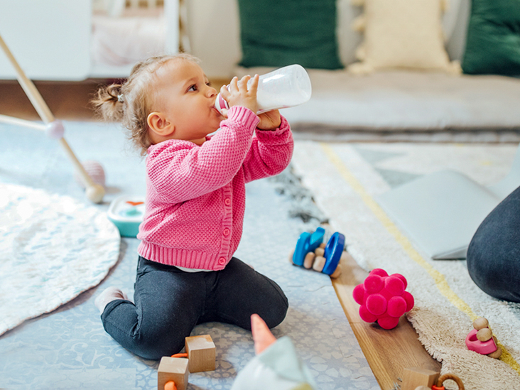 when do babies hold their own bottle